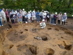 竪穴住居の説明。調査員の前にあるのは石囲炉(いしがこいろ)といって、食物の煮炊きや暖をとったり、明かりにしていたところで、今で言うキッチンのような場所です。