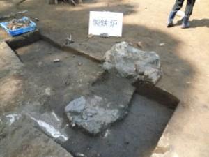 製鉄炉跡です。床面に見えるのは鉄滓(てっさい)という鉄生産時に出る鉄カスです。当時の鉄生産の様子が伺えます。