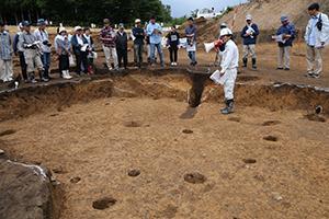 調査員が示した細長く色の濃い部分は、シカなどを狙った陥(おと)し穴で、縄文前期の竪穴住居跡にまたがり掘られています。住居や集落が一度なくなり自然に還ってから、約2000年後の縄文人が獣道に掘ったと思われます。(西調査区)