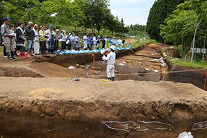 東調査区からは縄文中期末~後期前半の「捨て場」が見つかり、多数の石器や土器の破片がありました。ここから道路を挟んで、宮古市教育委員会様が発掘する調査区へと続いています。