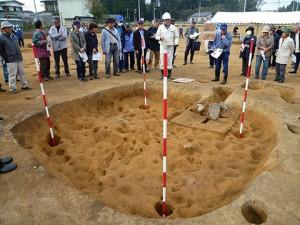 オープニングセレモニーの後、さっそく遺跡の説明です。奈良時代の竪穴住居跡です。床がデコボコですが、これは一回床をならすために荒く掘って地面を柔らかくするためだそうで、その掘り跡をはがすとこうなります。