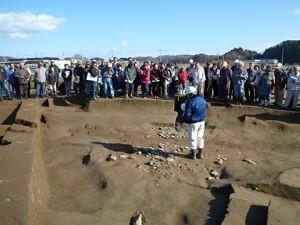 説明している調査員の足元には石がびっしりと敷かれています。ここは水が流れていたと思われる溝ですが、石の間には小さな土器片が無数にあり、刀や鉄製の農具も見つかっています。目的はなんだったのでしょうか?