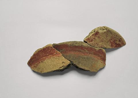 横線の文様が赤く塗られた壺の口縁部破片